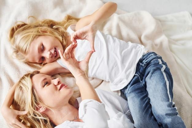 Mère avec sa fille allongée ensemble sur le lit blanc.