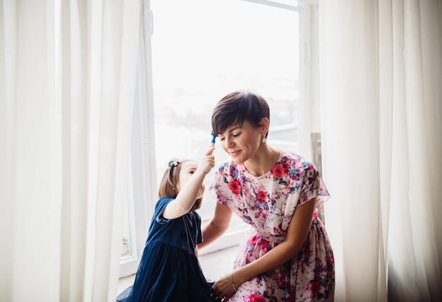 La mère avec sa fille assise sur le rebord de la fenêtre