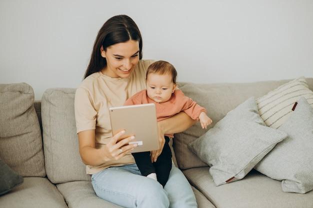 Mère avec sa fille bbay utilisant une tablette à la maison