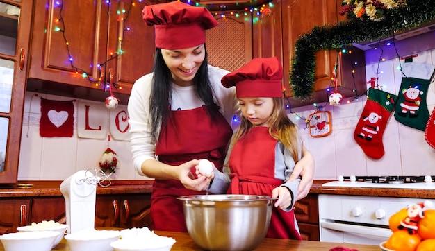 Mère avec sa fille cassant des oeufs dans un bol