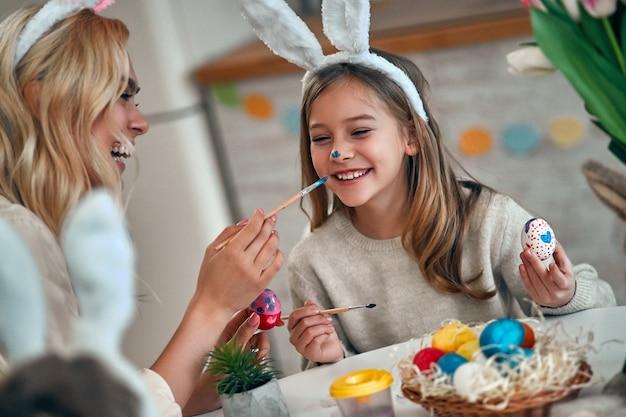 Une mère et sa fille célébrant pâques, peignant des œufs avec un pinceau. héhé, souriant et riant, dessinant sur le visage. jolie petite fille aux oreilles de lapin préparant les vacances.
