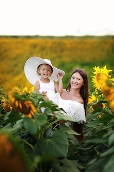 Mère avec sa fille dans un champ de tournesols