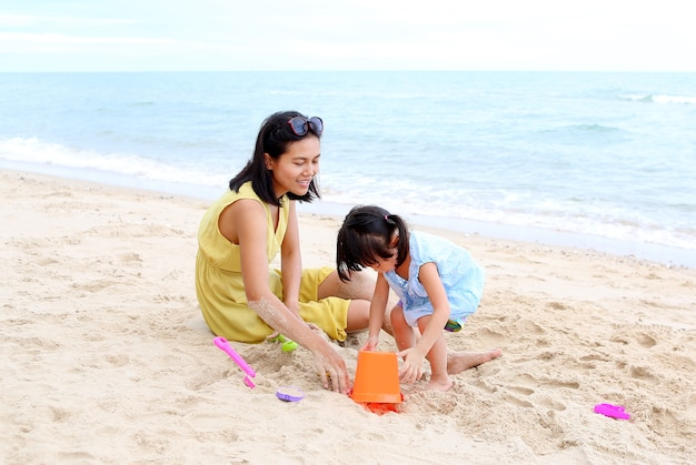 Mère et sa fille enfant fille jouant au sable avec un bloc d'animal formant à la plage