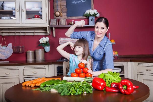 Une mère et sa fille heureuses aiment préparer et prendre des repas sains ensemble dans leur cuisine. ils préparent une salade de légumes et s'amusent ensemble. maman s'occupe de sa fille et apprend à cuisiner.