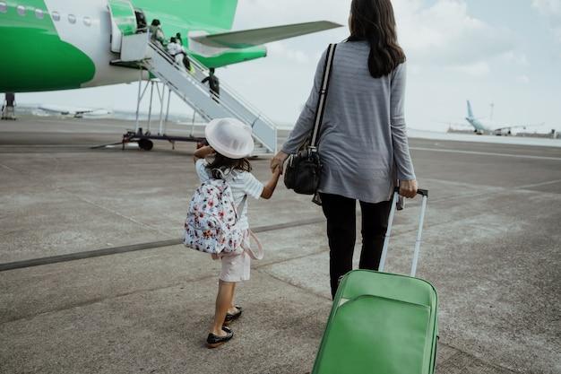 Une mère et sa fille joignent les mains marchant avec une valise