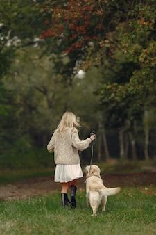 Mère et sa fille jouant avec un chien. famille dans le parc de l'automne. concept d'animal de compagnie, d'animal domestique et de mode de vie