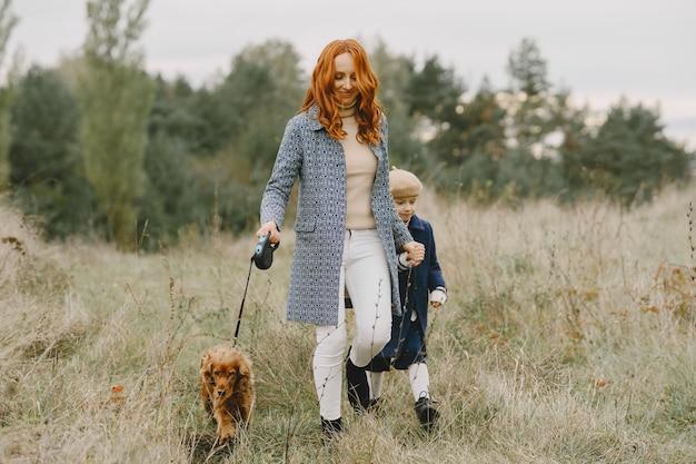 Mère et sa fille jouant avec un chien. famille dans le parc de l'automne. concept d'animal familier, animal domestique et mode de vie. temps de l'automne.