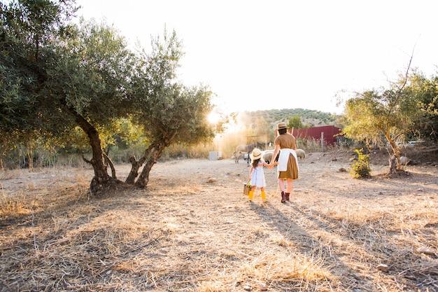 Mère et sa fille marchant dans le champ