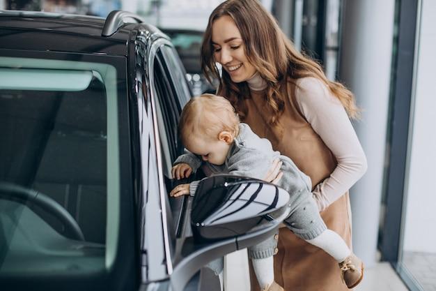 Mère avec sa petite fille dans une salle d'exposition automobile