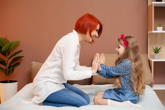 Mère et sa petite fille fille sur lit dans la chambre