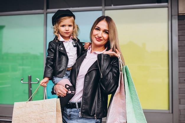 Mère avec sa petite fille mignonne avec des sacs