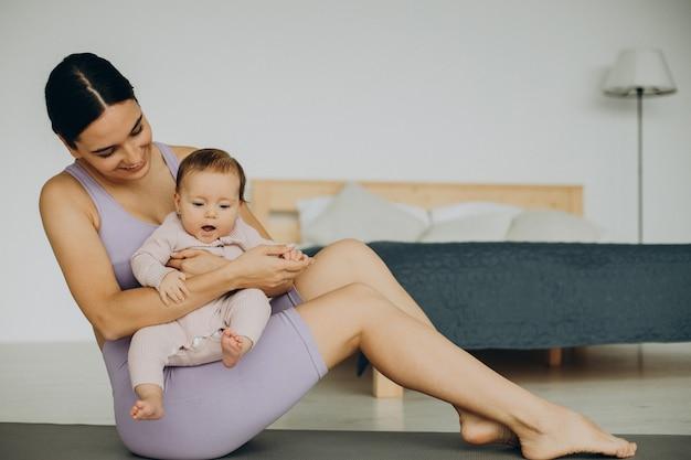 Mère avec sa petite fille pratique le yoga à la maison
