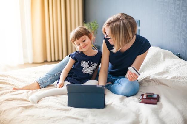 Mère et sa petite fille souriante, faire du shopping en ligne avec tablette et carte de crédit, assise sur un lit
