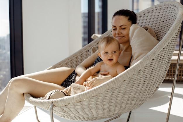 Mère se détendre avec bébé dans un fauteuil