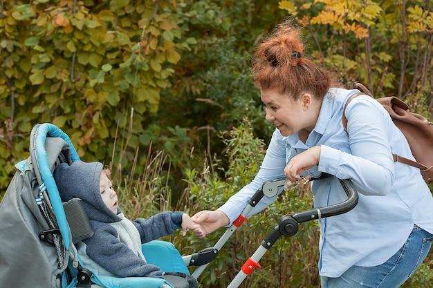 Mère se penche vers son fils handicapé dans un fauteuil roulant dans un parc de la ville