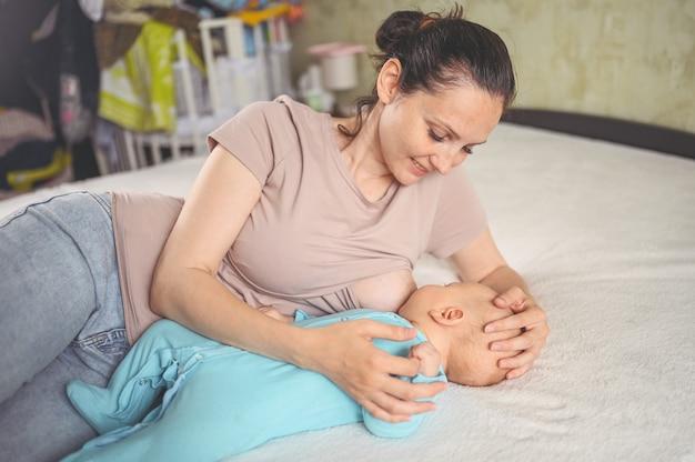 Mère se trouve avec bébé nouveau-né en combinaison bleue étreignant et l'allaite avec du lait maternel