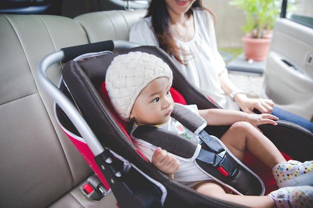 Mère sécurisant son bébé dans le siège auto dans sa voiture