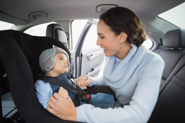 Mère sécurisant son bébé dans le siège d'auto