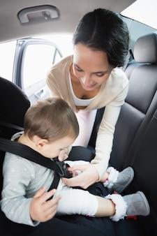 Mère sécurisant son bébé sur le siège auto