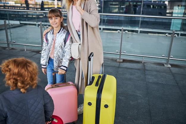 Mère serrant sa fille avec des sacs à roulettes à leurs pieds