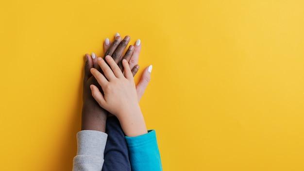 Mère et ses deux enfants, un caucasien un noir, empilant leurs mains