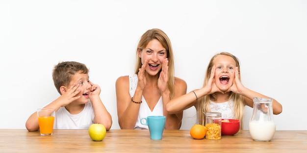 Mère avec ses deux enfants prenant son petit déjeuner et criant