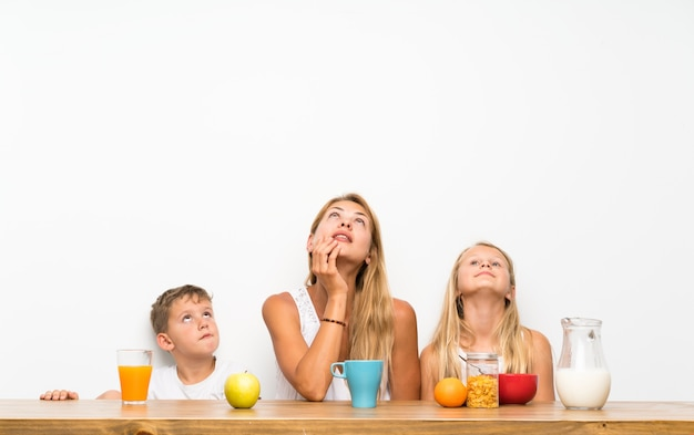 Mère avec ses deux enfants prenant son petit déjeuner en levant
