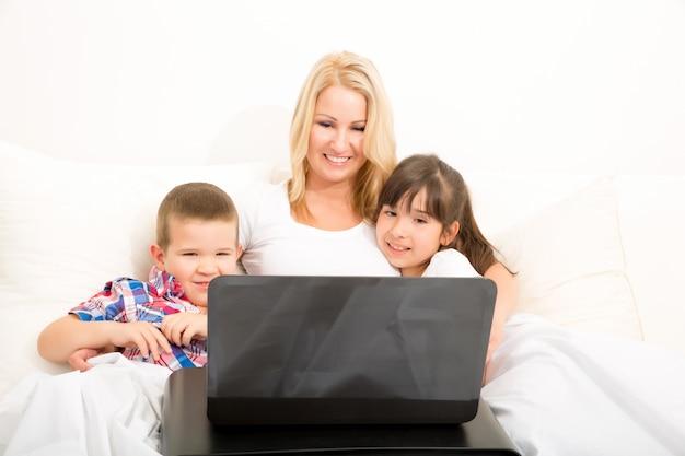 Mère avec ses enfants à l'aide d'un ordinateur portable au lit