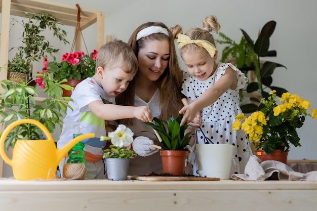 Mère avec ses enfants dans une plante à jeun ou transplanter des fleurs d'intérieur style de vie de jardinage à la maison