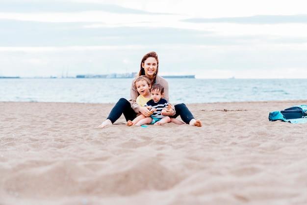 Mère avec ses enfants d'un et trois ans sur la plage un jour d'été nuageux. mère célibataire