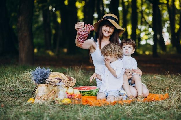 Mère avec ses fils ayant pique-nique en forêt
