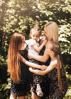 Une mère et ses trois filles se blottissent en été dans la nature. famille nombreuse. passer du temps à l'extérieur, vie de famille heureuse