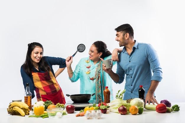 Mère ou soeur active indienne faisant foor pour fils et fille dans la cuisine