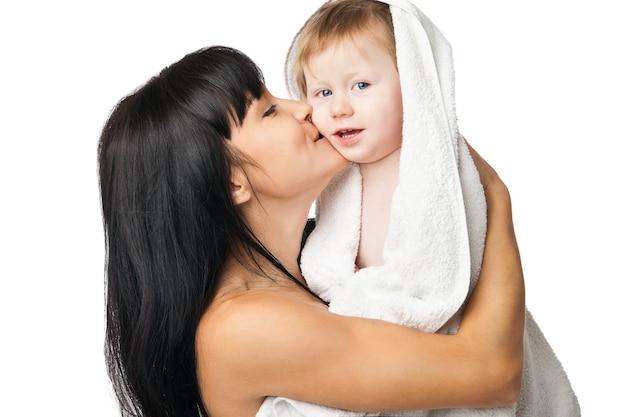Mère avec son bébé après s'être baigné dans une serviette blanche