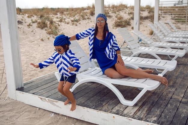 Mère et son bébé dans des vestes bleues à rayures marchent le long de la plage à côté d'un belvédère en bois