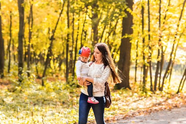 Mère avec son bébé. maman et fille dans un parc en automne.