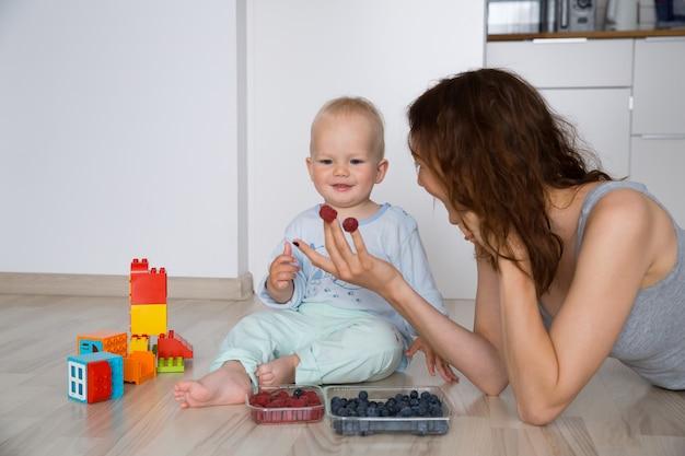 Mère avec son enfant mangeant ensemble et s'amusant