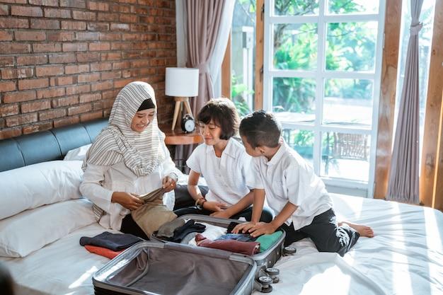 La mère et son enfant préparent des vêtements et mettent dans une valise pour être transportés lorsque mudik