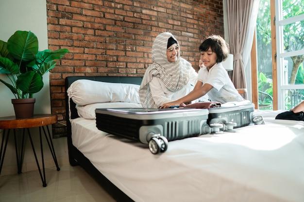 La mère et son enfant préparent des vêtements et les mettent dans une valise
