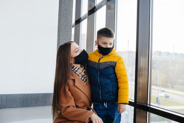 Une mère avec son enfant se tient dans un masque pendant la quarantaine. pandémie, coronavirus.