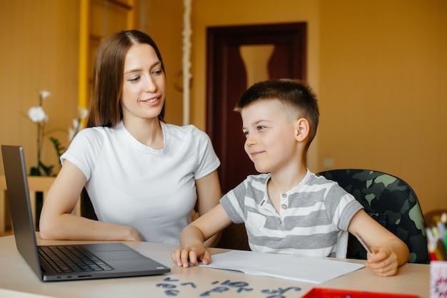 Une mère et son enfant suivent une formation à distance à la maison devant l'ordinateur. restez à la maison, entraînez-vous.