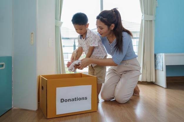 Une mère et son fils asiatiques se tiennent près d'un placard de vêtements dans le vestiaire, portant une boîte de vêtements donnée à apporter au centre de dons.
