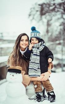 La mère et son fils assis près de bonhomme de neige