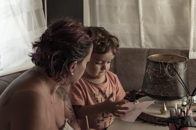 Une mère et son fils caucasien d'un an font de l'artisanat dans une caravane pendant leurs vacances