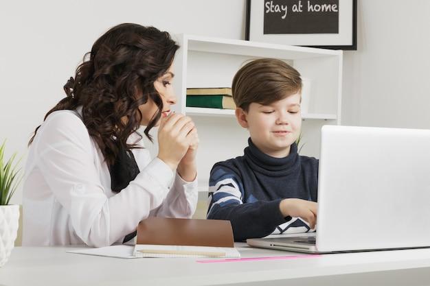 Mère et son fils font leurs devoirs dans la salle blanche. taper des devoirs sur un ordinateur portable.