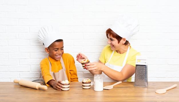 Mère et son fils habillés en chef dans une cuisine