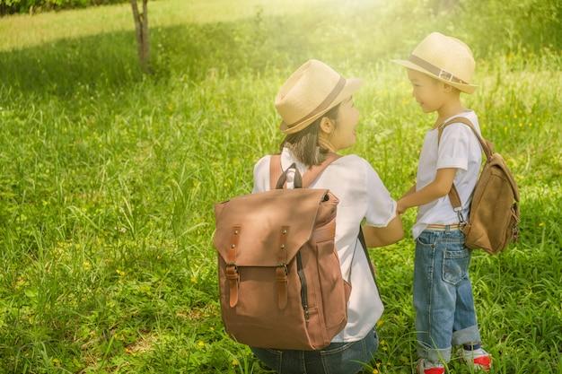 Une mère et son fils parlent dans les champs d'herbe en plein air