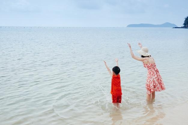 Une mère et son fils sur la plage en plein air mer et ciel bleu