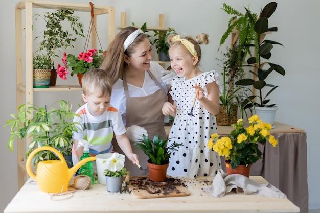 Mère avec son fils et sa fille dans une plante à jeun ou transplanter des fleurs d'intérieur style de vie