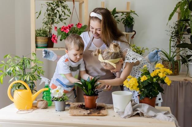 Mère avec son fils et sa fille dans une plante à jeun ou transplanter des fleurs d'intérieur
